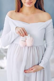 Schöne schwangere frau in einem weißen kleid, das babyschuhe hält