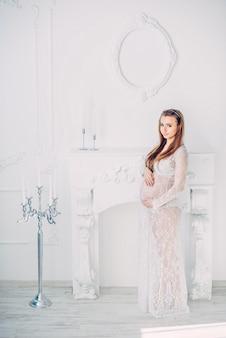 Schöne schwangere frau in einem weißen spitzen-peignoir, das nahe weißem kamin bleibt und auf schwangerem bauch hält