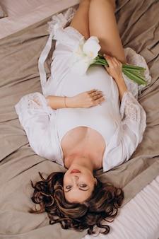 Schöne schwangere frau in weißer kleidung ansicht von oben gesundheitswesen