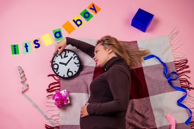 Schöne schwangere frau liegt auf dem boden auf einem karierten bauch und schaut auf uhr und karten mit der aufschrift es ist ein junge in studio-rosa-hintergrundansicht von oben. warten auf die geburt.