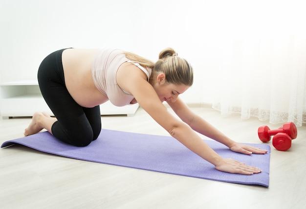 Schöne schwangere frau macht yoga-übungen auf fitnessmatte im wohnzimmer living