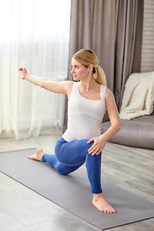 Schöne schwangere frau mit großem bauch, die gymnastikübungen für das strecken mit vergnügen tut