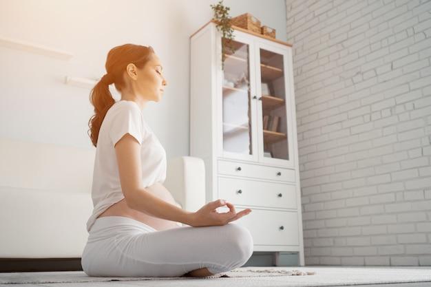 Schöne schwangere frau mit großem nacktem bauch meditiert im lotussitz zu hause sitzen
