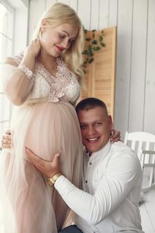 Schöne schwangere frau mit ihrem ehemann in einem studio