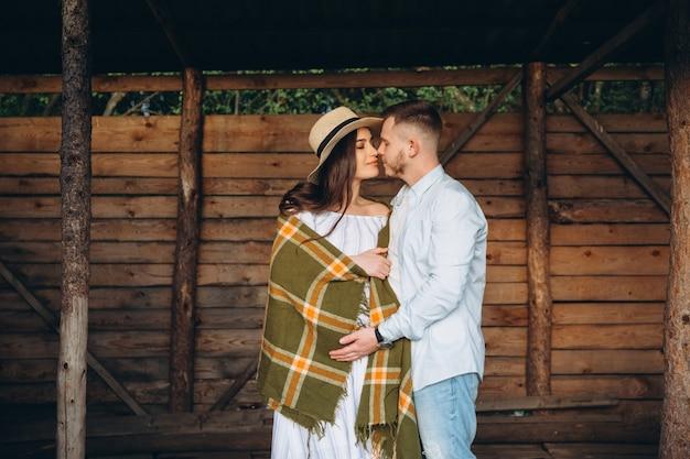 Schöne schwangere frau und ihr ehemann, die nahe holzgebäude aufwerfen. stilvolles glückliches paar lieben sich. mode und rustikaler stil.