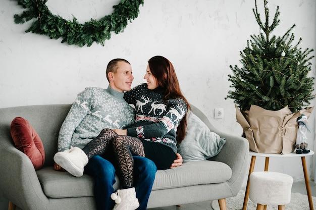 Schöne schwangere frau und mann in weichen pullovern auf sofa nahe baum. frohes neues jahr und frohe weihnachten. weihnachten dekoriertes interieur. konzept für schwangerschaft, urlaub, menschen und erwartung. nahansicht.