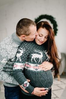 Schöne schwangere frau und mann in weichen pullovern nahe baum. frohes neues jahr und frohe weihnachten. weihnachten dekoriertes interieur. konzept für schwangerschaft, urlaub, menschen und erwartung. nahansicht.