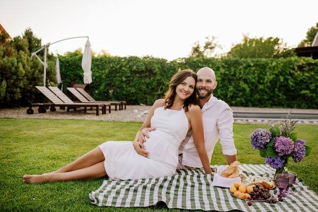 Schöne schwangere frau und mann sitzen auf grünem rasen