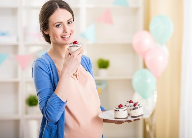 Schöne schwangere frau wird einen kuchen essen.