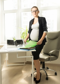 Schöne schwangere geschäftsfrau, die am schreibtisch steht und in die kamera schaut