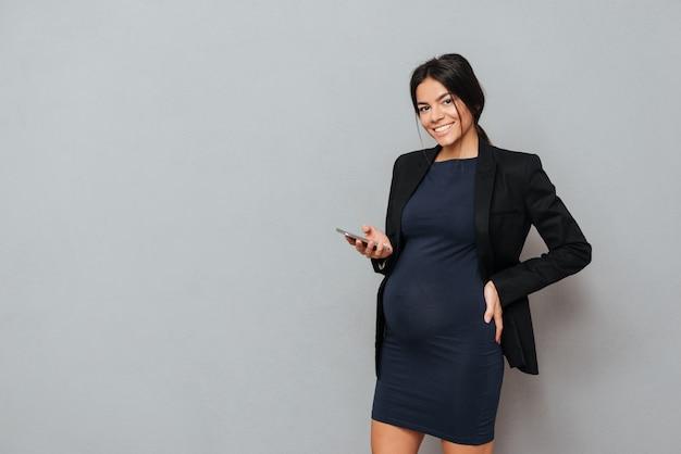 Schöne schwangere geschäftsfrau mit handy.