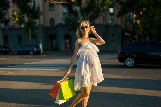 Schöne schwangere junge frau, die einkaufstaschen hält