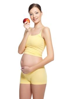 Schöne schwangere junge frau mit hübschem magen, der roten apfel lokalisiert auf weiß hält