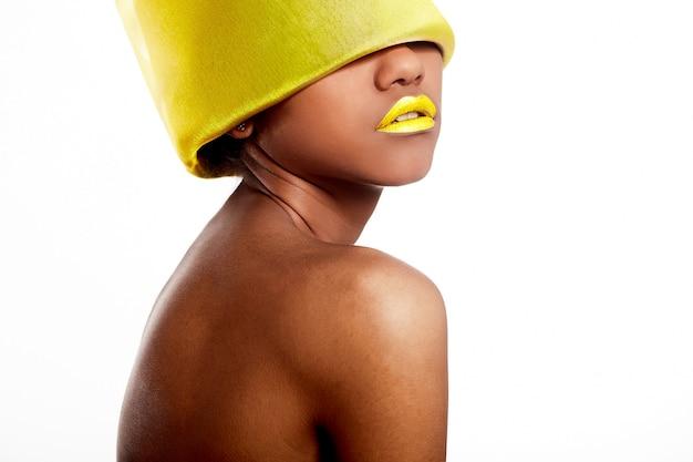Schöne schwarze amerikanerin der mode des hohen modeblick.glamour mit den gelben hellen lippen mit gelbem material auf dem kopf lokalisiert auf weiß
