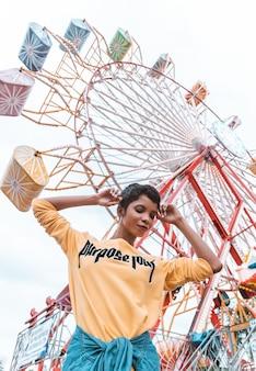 Schöne schwarze frau, die gelbes sweatshirt in einem vergnügungspark trägt
