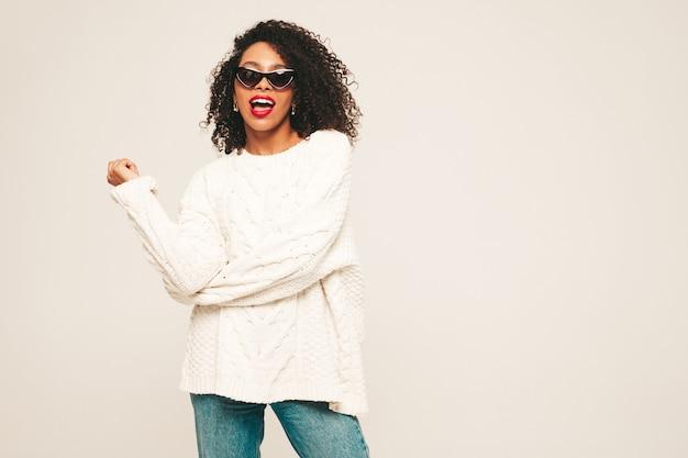 Schöne schwarze frau mit afro-locken-frisur und roten lippen. lächelndes modell in trendiger jeanskleidung und winterpullover.