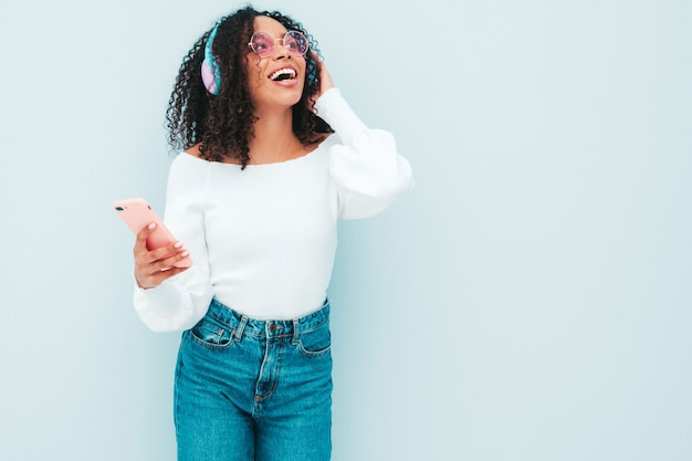 Schöne schwarze frau mit afrolockenfrisur. lächelndes modell in pullover und jeans. sorglos weibliches hören von musik in drahtlosen kopfhörern