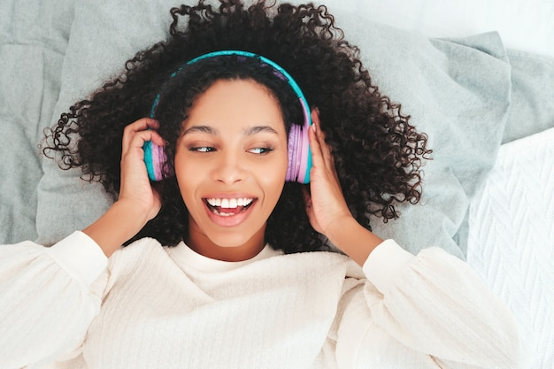 Schöne schwarze frau mit afrolockenfrisur. lächelndes modell in pullover und jeans. sorgloses weibliches hören von musik in drahtlosen kopfhörern am morgen
