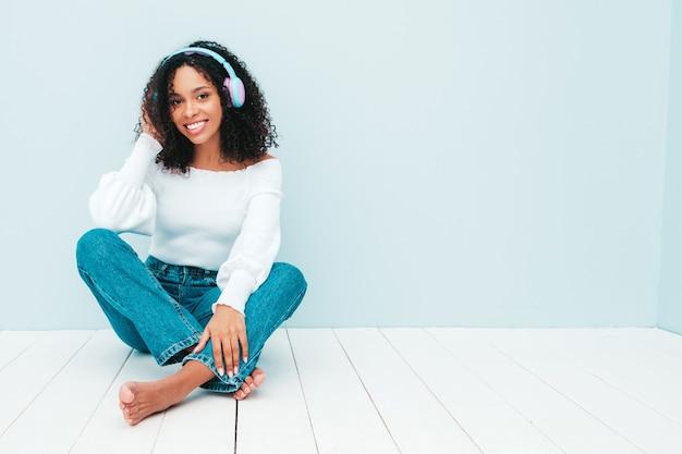 Schöne schwarze frau mit afrolockenfrisur. lächelndes modell in pullover und jeans