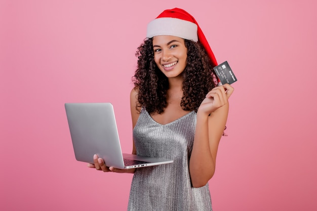 Schöne schwarze frau mit der kreditkarte und laptop, die feiertag sankt-hut und -kleid tragen