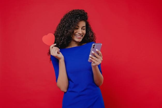 Schöne schwarze frau mit herzen formte die valentinsgrußkarte, die telefon auf roter wand betrachtet