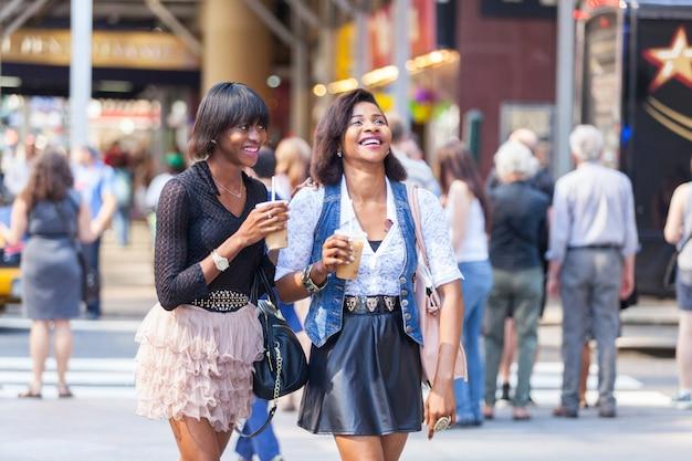 Schöne schwarze frau zwei, die auffrischungsgetränke in new york genießt