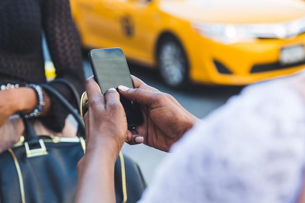 Schöne schwarze frau zwei, die intelligentes telefon in new york verwendet