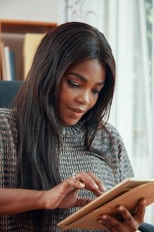 Schöne schwarze geschäftsfrau, die tablette verwendet