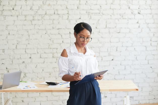 Schöne schwarze junge frau in der eleganten freizeitkleidung, die diagramm beim stehen im büro betrachtet.