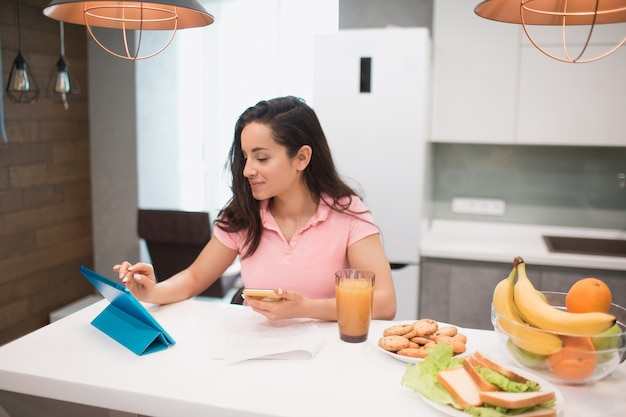 Schöne schwarzhaarige frau arbeitet von zu hause aus. ein mitarbeiter sitzt in der küche und hat viel arbeit an einem laptop und tablet sowie videokonferenzen und besprechungen.