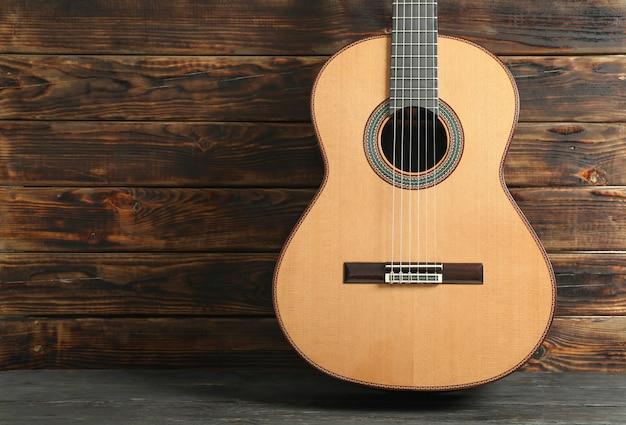 Schöne sechssaitige klassische gitarre gegen holztisch