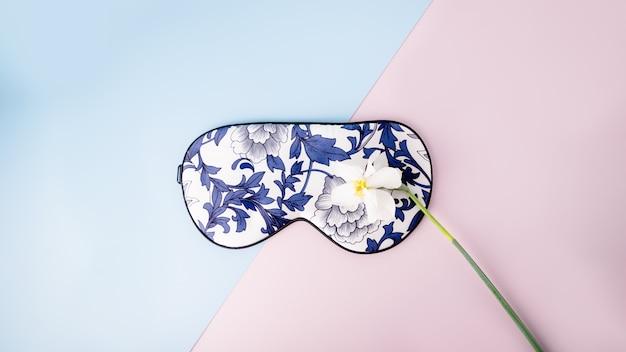 Schöne seidenschlafmaske für die augen mit blumenmuster und weißer narzissen- oder narzissenblüte auf rosa blauem hintergrund, panorama