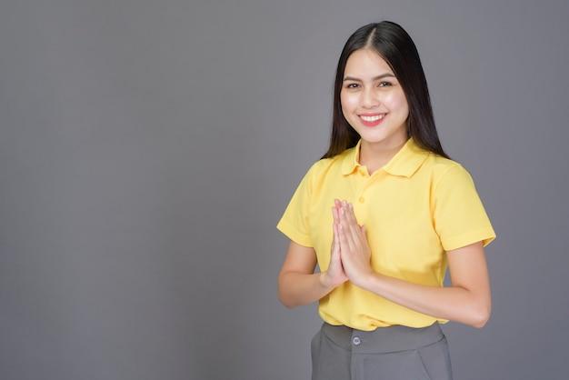 Schöne selbstbewusste frau grüßt (thai wai), um respekt über grau zu zeigen