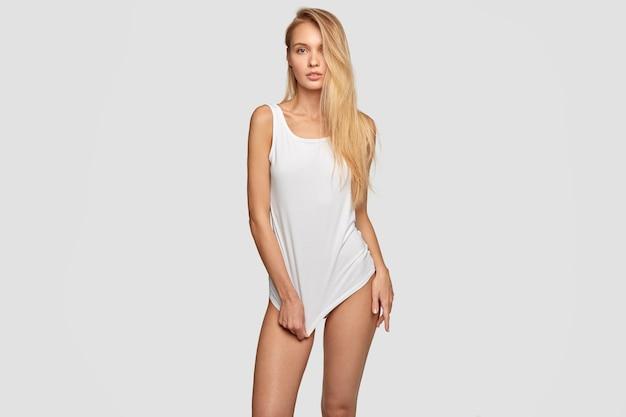 Schöne sexuelle frau im übergroßen langen t-shirt mit nachgebildeter leerstelle, hat schlanke beine, posiert gegen wand, hat gesunde haut, hat lange haare, macht foto für modemagazin. isolierter schuss