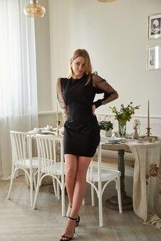 Schöne sexy blondine in einem kurzen schwarzen kleid in einer wohnung