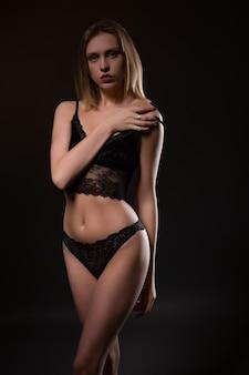 Schöne, sexy blondine in schwarzer spitzenunterwäsche