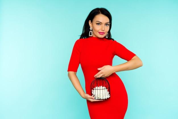 Schöne sexy brünette frau im roten kleid, die einen vogelkäfig mit einer blume hält