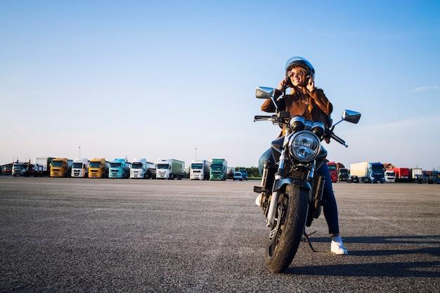 Schöne sexy brünette frau in der lederjacke, die auf retro-artmotorrad sitzt und sich auf die fahrt vorbereitet
