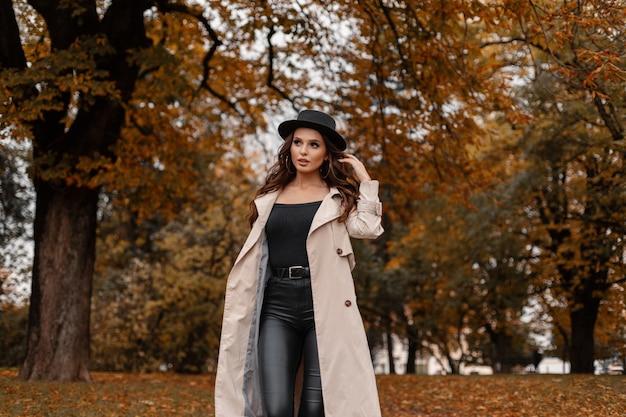 Schöne sexy brünette frau mit lockigem haar in modischer kleidung mit klassischem mantel, hut und lederhose geht im park mit goldenem herbstlaub