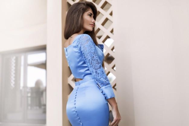 Schöne sexy brünette steht in der nähe des pools in dem langen blau getrennten kleid, frau mit langen haaren, perfektem körper und hübschem gesicht, make-up, unter palmen