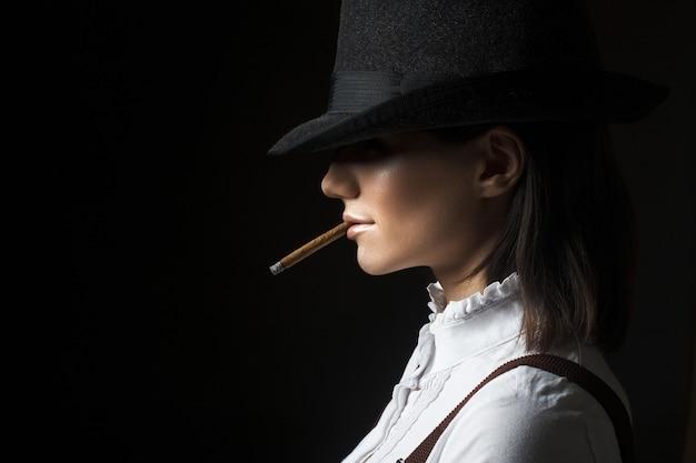 Schöne sexy brunettefrau in rauchender zigarette des hutes