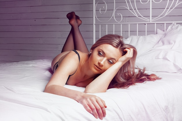 Schöne sexy dame im eleganten schwarzen schlüpfer und in den strümpfen im bett
