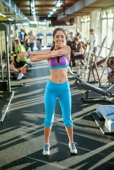 Schöne sexy fit mädchen, die ihre armmuskeln vor dem training im fitnessstudio dehnen
