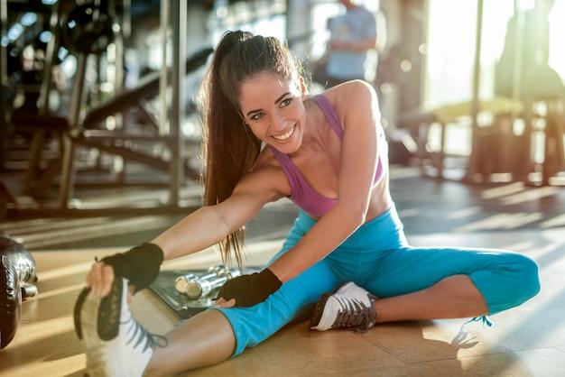 Schöne sexy fit mädchen, die ihre beinmuskeln vor dem training im fitnessstudio dehnen
