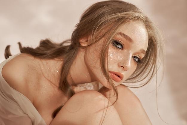 Schöne sexy frau, die auf dem boden sitzt, kosmetik und make-up auf dem gesicht und körper des mädchens
