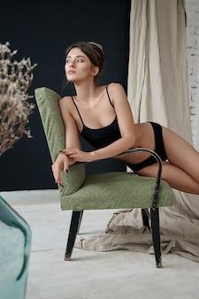 Schöne sexy frau, die auf einem stuhl sitzt. schönes lächeln, natürliches make-up