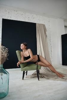 Schöne sexy frau, die auf einem stuhl sitzt