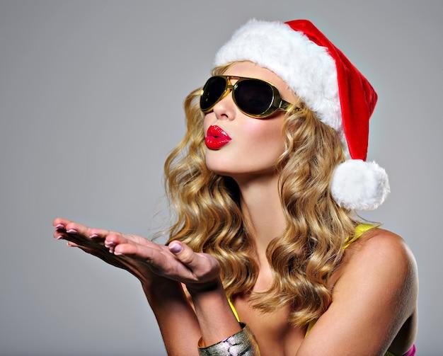 Schöne sexy frau, die im weihnachtsmannhut lächelt.