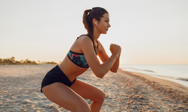 Schöne sexy frau, die sport am strand, sonnenaufgang, morgenübungen macht, musik über kopfhörer hört, gesunden lebensstil, joggen,