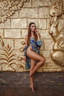 Schöne sexy frau im designer-badeanzug nahe der goldenen wand